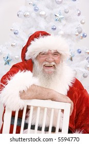 Laughing Santa sitting on a chair in front of the christmas tree