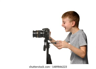 Laughing schoolboy shoots video on DSLR camera. Side view. White background, isolate