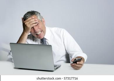 laughing senior businessman computer phone hand gesture on head