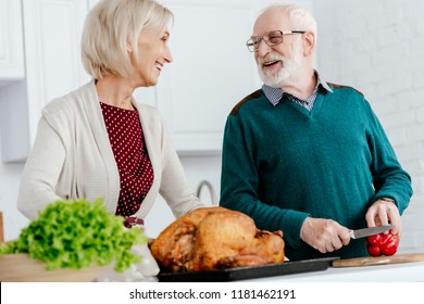 laughing senior couple cooking thanksgiving turkey together and looking at each other