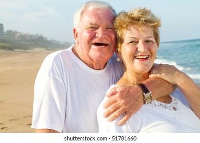 laughing senior couple hugging on beach