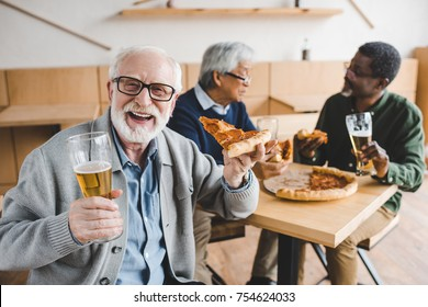 laughing senior man eating pizza with beer while his friends talking on background