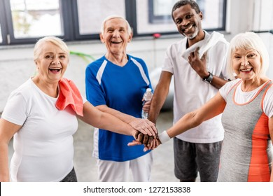 laughing senior multiculutral sportspeople putting hands together at sports hall