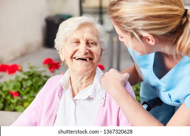 Laughing senior woman and caring geriatric nurse together in nursing home