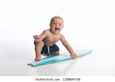 A laughing seven month old baby boy playing with a tiny surfboard. Shot in the studio on a white, seamless backdrop.