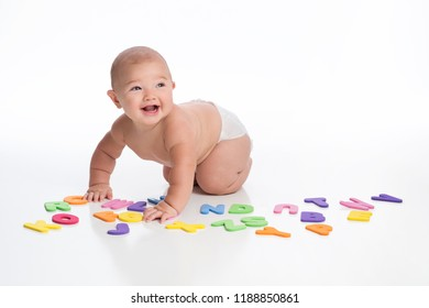 A laughing seven month old baby boy playing with foam alphabet toys. Shot in the studio on a white, seamless backdrop.