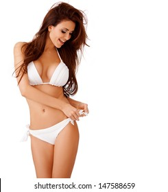 Laughing sexy busty young brunette woman in a white bikini playing with the bow on her hip  three quarter isolated studio portrait