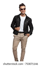 laughing sexy man wearing sunglasses and leather jacket looks to side on white background