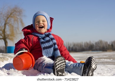 Laughing small child in the winter on snow