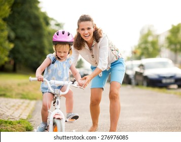 A laughing, smiling mother pushes her daughter forward on a warm summer's day as she teaches her how to ride her bicycle on a city sidewalk near a green park.