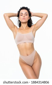 Laughing sporty girl in bikini posing on grey background. Photo of attractive woman with slim toned body. Beauty and body care concept