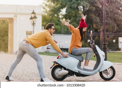 Laughing sporty guy pushing scooter with stylish girl on it. Pretty young lady in red hat riding in park, enjoying date with handsome man.