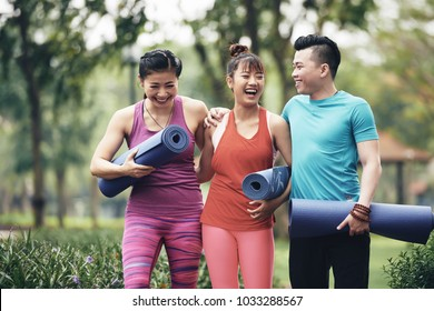 Laughing sporty Vietnamese young women with yoga mats