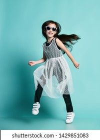 Laughing stylish asian baby girl kid in high fashion black and white clothes and sunglasses jumps dances cool in gangnam style at birthday party on blue mint background