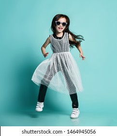 Laughing stylish asian baby girl kid in modern clothes and sunglasses jumps dances cool in gangnam style at party having fun makes show on blue mint background