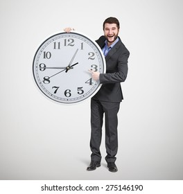 laughing successful businessman in formal wear pointing at clock dial and looking at camera over light grey background