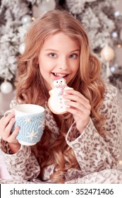 Laughing teen girl 12-15 year old biting cookie, drinking tea in room. Christmas tree. Celebration.