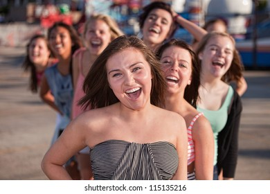 Laughing teenage friends behind one another outside
