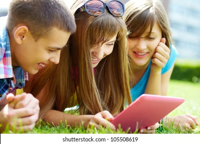 Laughing teenagers looking at the touchpad screen outdoors