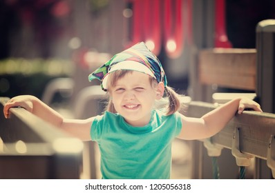 laughing three-year girl at playground area in sunny summer day