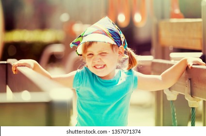 laughing three-year girl at playground area in sunny  day