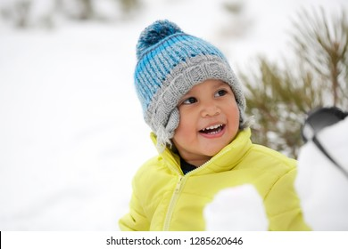 Laughing toddler boy wearing winter clothes in a snow covered mountain.