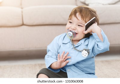 Laughing toddler chewing nipple and talking on mobile phone, sitting on floor at home, copy space