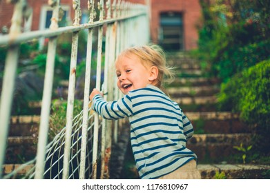 A laughing toddler is playing in the garden at the front of his house