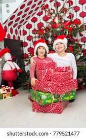 Laughing two kids with Christmas presents in front of tree in their home