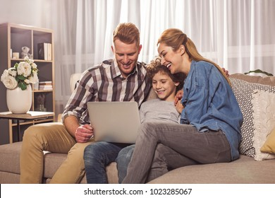 Laughing unshaven husband and beaming wife with cheerful boy watching at notebook computer. Entertainment concept