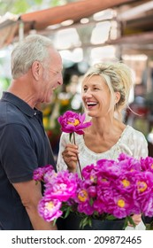Laughing vivacious middle-aged couple celebrating with a large bunch of colorful magenta flowers outdoors in an urban environment