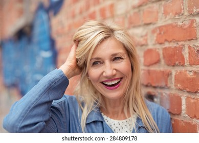 Laughing vivacious middle-aged woman mussing her long blond hair with her hand as she stands in front of a brick wall outdoors