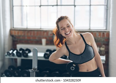 Laughing vivacious young woman in a gym working out with a pair of dumbbells in a health and fitness concept
