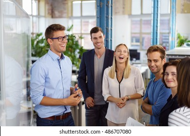 Laughing white collar workers standing around white board during meeting in small office