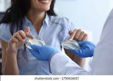 Laughing woman chooses breast implants from doctor. Doctor offers girl choice silicone breast implants. Medical consultation or recommendation plastic surgeon. Enlarge the breast and change its shape