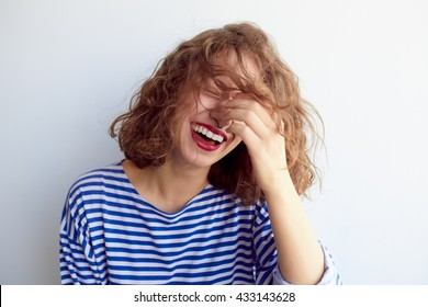 Laughing woman in marine shirt with curly hair over white wall. Toothy smile and red lips.