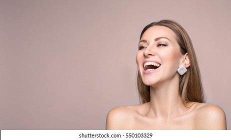 Laughing woman in marine shirt with curly hair over white wall. Toothy smile and red lips. Close up portrait of a beautiful middle aged woman laughing