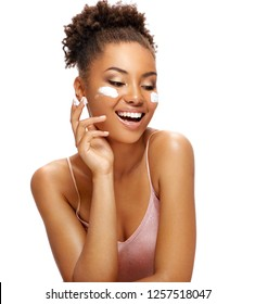 Laughing woman with moisturizing cream on her face. Photo of african american woman with flawless skin on white background. Skin care and beauty concept