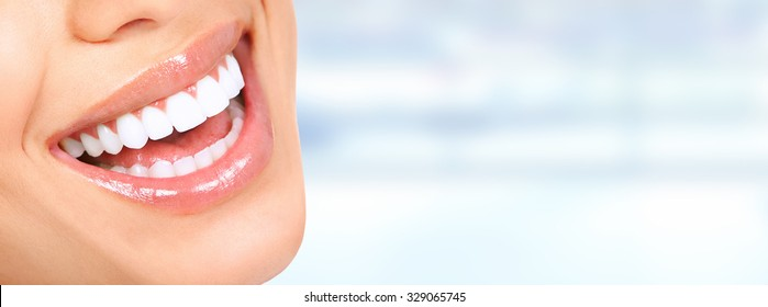 Photo of Laughing woman mouth with great teeth over blue background.