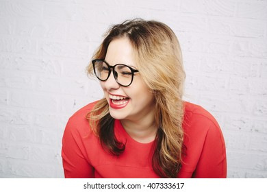 Laughing woman in red dress and glasses on white brick wall background