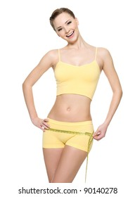 Laughing woman with sexy slim body measuring hips with  measurement type - isolated on white.
