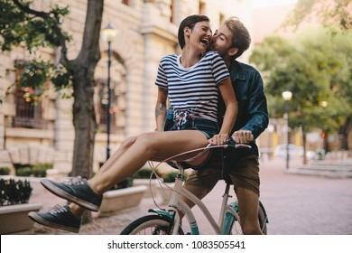 Laughing woman sitting on boyfriends bicycle handlebar. Cheerful couple on a bike together in the city having fun.
