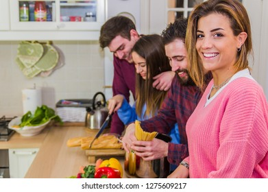 Laughing woman smiling at the camera talking and preparing meals at table with friends full of vegetables and pasta