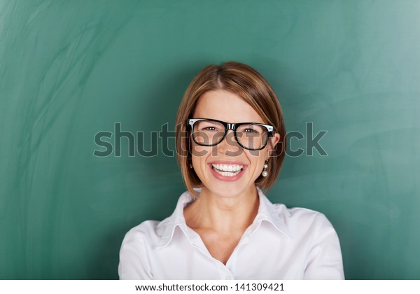 Laughing woman wearing glasses and standing in font of a class blackboard