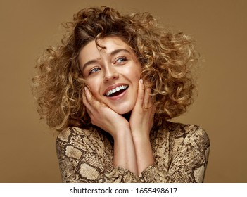 Laughing woman with white teeth and curly hair touching cheeks. Beauty portrait of female face with healthy natural skin