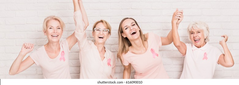 Laughing women with breast cancer ribbons standing against brick wall