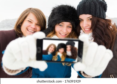 Laughing women taking photos with phone camera - winter selfie time.