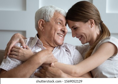 Laughing young 30s woman embracing happy older father, sitting together on couch at home. Smiling two generations communicating, sharing news, having fun, enjoying family weekend time indoors.