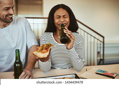 Laughing young African American businesswoman sitting with a coworker in an office after work drinking a beer and eating pizza