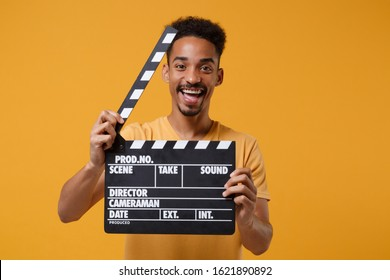 Laughing young african american guy in casual t-shirt posing isolated on yellow orange background in studio. People lifestyle concept. Mock up copy space. Hold classic black film making clapperboard